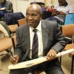 A proud John Shepherd signing the raffled bat. Photo courtesy CaribDirect