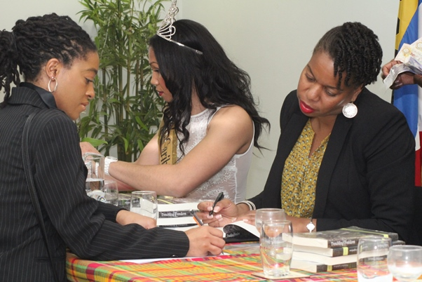 Natasha speaks with interested member of the audience with Ms Caribbean UK in background. Photo courtesy CaribDirec